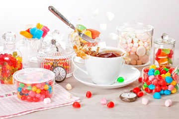 Cup of tea with assorted colorful candies, flying spoon, sugar and splashes for kid's birthday