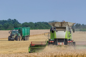 AGRICULTURAL MACHINERY - Harvester and tractor on the field