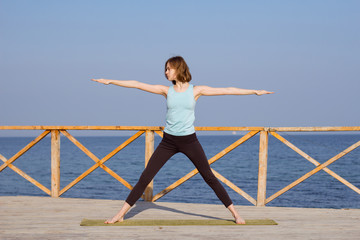 beautiful young woman  practice yoga exercise on the wooden pier, sea background