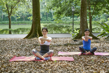 Two friends practising Yoga at Botanic Gardens, Singapore