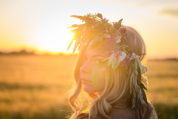 portraits of young woman having good time in wheat field during sunset, lady in head flower wreath during