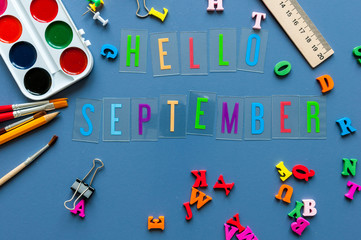 Hello September text on teacher or pupil table with school supplies side border on a blue background