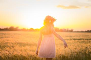 beautiful blonde lady in head flower wreath during sunrise in summer wheat fields