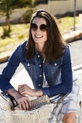 Denim jacket brunette in sunglasses on bicycle, smiling