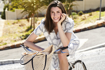 Portrait of young brunette on bicycle, smiling
