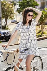 Summer dress girl on bicycle, looking away