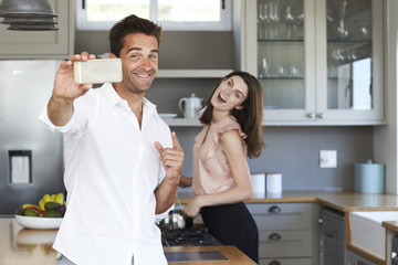Couple in kitchen posing for selfie, smiling