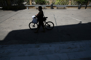 A man with a bike walks in the old city of Nicosia