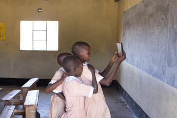 School girls using tablet in classroom. Kenya, Africa.