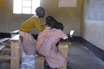 School girls in classroom, looking at tablet. Kenya, Africa.