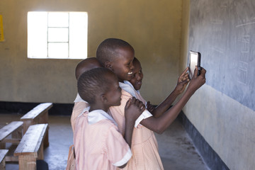 School girls using tablet to take selfie. Kenya, Africa