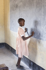 School girl writing on blackboard in classroom