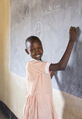 Smiling school girl using chalkboard in classroom. Kenya, Africa