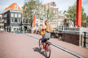 Young beautiful woman riding a bicycle with bag and bouquet of tulips on the bridge over the water channel in Amsterdam old city
