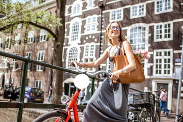 Young beautiful woman standing with red bicycle and bouguet of tulips on the bridge over the water channel in Amsterdam old city