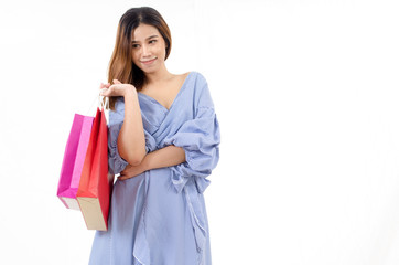 portrait of cheerful asian young woman in blue dress holding shopping bags isolated on white background, online shopping, lifestyle technology concept, soft focus