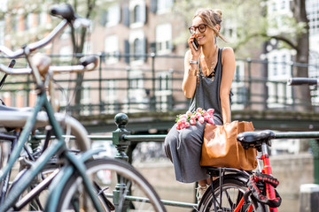 Young woman talking with smart phone sitting with bag and flowers near the water channel in Amsterdam old city