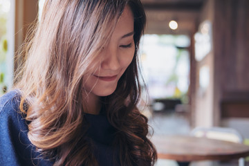 Closeup portrait image of a smiley beautiful Asian woman with feeling good sitting and relaxing in modern cafe