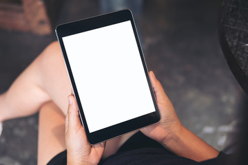Mockup image of woman's hands holding black tablet pc with blank white screen on thigh with concrete floor background in modern cafe
