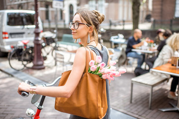 Young beautiful woman walking with bicycle holding bag and bouquet of tulips on the street near the water channel in Amsterdam old city