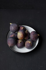 figs in a bowl on a black background