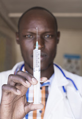 Doctor using needle and syringe. Kenya, Africa