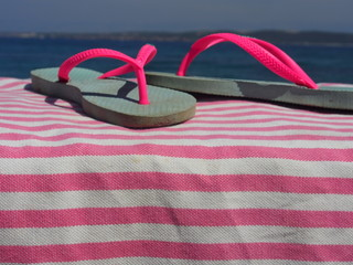 Badeurlaub: Rosa Kinder-Flip-Flops auf Strandtuch