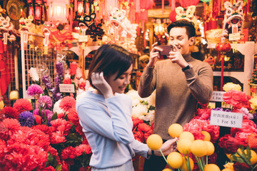 Man taking a photo of his partner shopping in Chinatown, Singapore