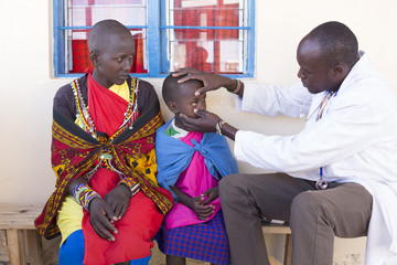 Doctor examining child patient (Maasai tribe). Kenya, Africa.