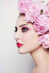 Young beautiful woman with stylish make-up and peonies in her hair, copy space