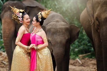 Pretty thai girls in traditional thai costumes with elephants