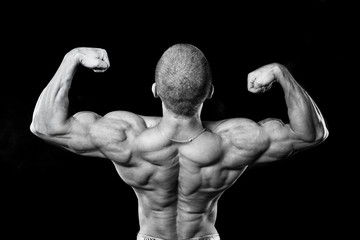 Back muscles. The athlete flexes his muscles. Bodybuilder presenting his body.