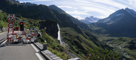 beautiful road by a waterfall and the mountains