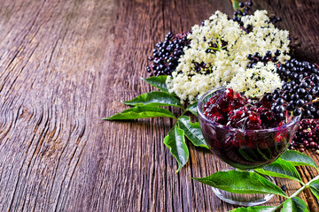 Toasts with elderberry jam and fresh berry fruits on wooden table. Free space for your text.