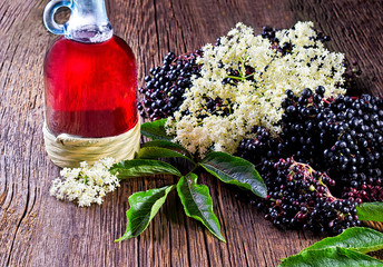 Bottle with elderberry juice and fresh berry fruits on wooden table.