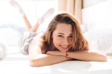 Cheerful carefree woman smiling to camera in bed Wall mural