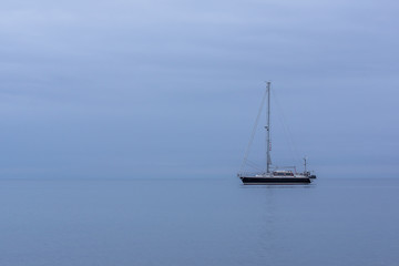 Sailing boat in blue twilight hour, alone in the ocean