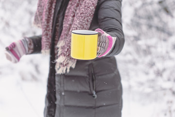 Woman holding yellow mug of hot drink outdoors