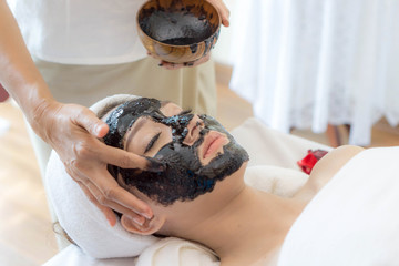 beautiful and healthy young woman relaxing with face massage skin care health black mask at beauty spa salon