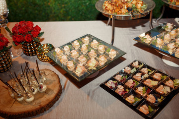 Square plates with shrimps and other snacks stand served on grey tablecloth