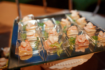 Little glass plates with shrimps and greenery