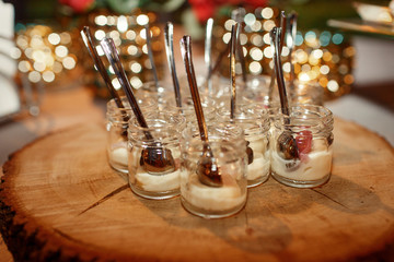 Little bottles with sauces and spoons stand served on wooden dish