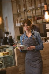 Waitress holding digital tablet in café