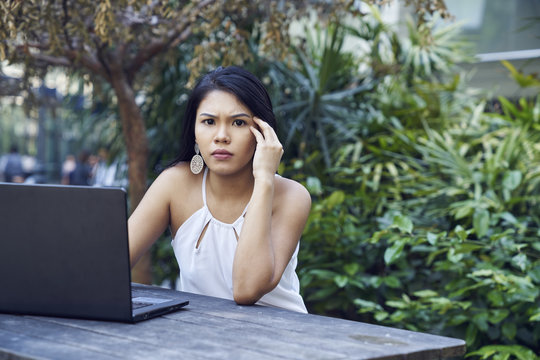 Pretty Malay woman frustrated while working on her laptop
