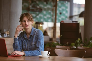 Beautiful woman talking on mobile phone while using laptop