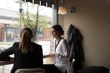 Friends sitting by window in cafe