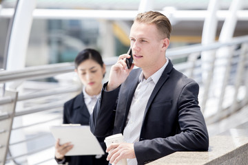 Businessman using Smartphone for Work, Man Working Concept, Business walking while talk for Business and Secretary follow him.