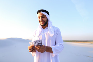 Successful Arab sheikh considers banknotes and happy, standing i