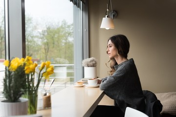 Thoughtful young woman having coffee at table in cafe
