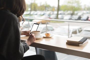 Woman using phone while having coffee